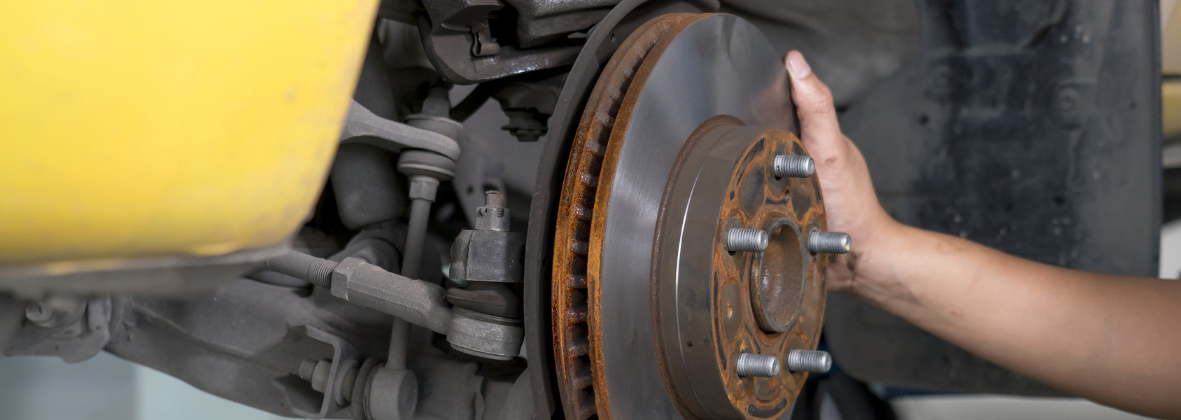Car mechanic replacing wheel brake shoes of lifted automobile at repair service station.
